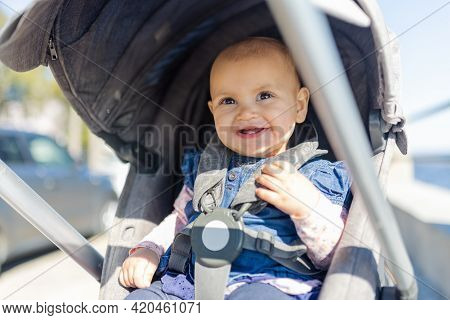Adorably Happy Baby In Gray Stroller With Blurry Background