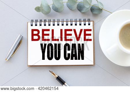Believe You Can. Text On White Notepad Paper. Near Cups With Coffee And Plants On A Gray Background.