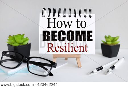 How To Become Resilient. Text On White Paper, Notebook On A Stand On A Light Background Near Glasses