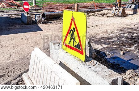 Under Construction Road Sign On The Closed Road At The City Street, Stop Sign. Caution Symbol Under