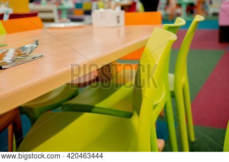 Indoor Cafe With Plastic Furniture. Green Chairs And Orange Table. Empty. Restaurant. Colourful. Cat