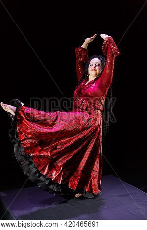 Gypsy Woman With Curly Black Hair In A Red Dress In Motion On A Black Background. Vertical Photo