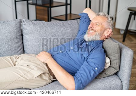 Serene Grey-haired Hipster Guy Rests On The Couch In Cozy Living Room, Mature Man Lying Down On The