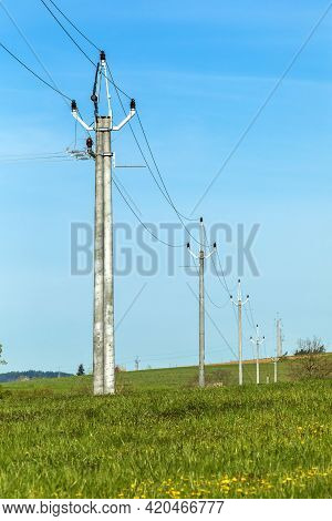 Power Lines In The Countryside Against Blue Sky In Spring Day. Electricity Distribution In The Czech
