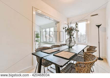 Sofa And Table With Decorations Placed Near Marble Fireplace Behind Doorway Of Dining Room In Elegan