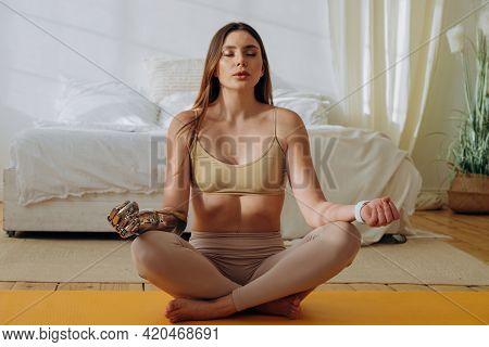 Woman With Metal Prosthesis Arm Meditates On Yellow Mat