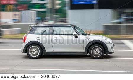 Silver Mini Cooper Is Moving Fast Along A City Street. Moscow, Russia - April 2021
