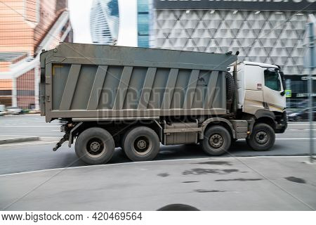 Gray Truck Is Running On The Street In City. Recycling Truck Rides On The Urban Road. Collection And