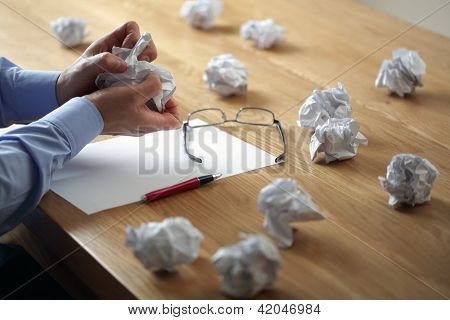 Tearing up another crumpled paper ball for the pile