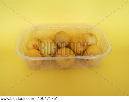 Lemon Fruits In Plastic Box Over Yellow Background
