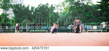 Exercise And Relaxing Time With Family Concept. Mom And Daughter Make Gestures Start To Run A Race O