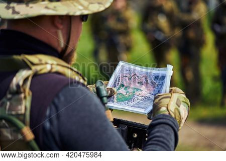 Close-up Shot Of An Airsoft Player In Military Uniform Examining A Map