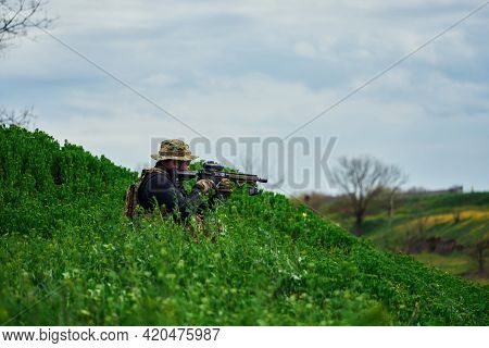 Airsoft Player In Military Uniform Sits In The Grass And Aims At The Rifle Scope