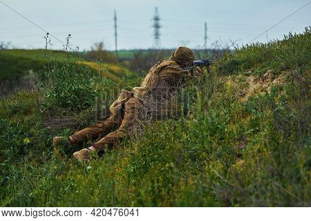 The Soldier Lies On The Ground And Aims At The Rifle Scope