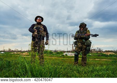 Two Airsoft Players With Weapons In Their Hands Stand In The Field