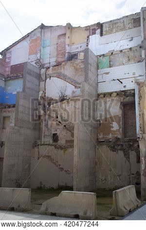 Wall Of Half-destroyed Old Building Reinforced With Concrete Supports. Outlines Of Old Staircases An