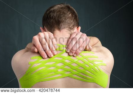 Hands Of Young Man Holding His Neck With Striped Kinesiology Medical Tape Applied To Relieve Back Pa