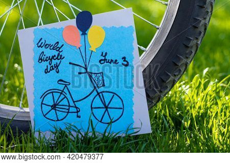 Handmade Colored Paper Greeting Card Next To A Bicycle Wheel On Grass Background. Diy. World Bicycle