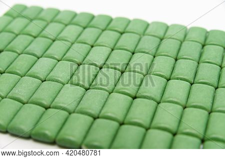 Green Mint Chewing Gum Tablets Aligned. Isolated On White Background. Close-up.
