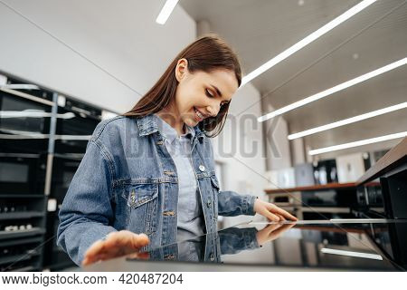 Young Brunette Woman Choosing New Electric Stove In A Hypermarket