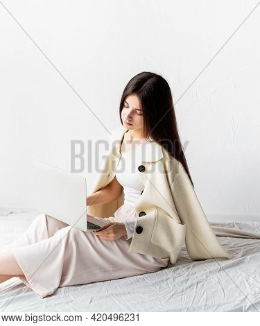 Beautiful Young Woman Sitting On The Floor And Doing Freelance Project On Laptop