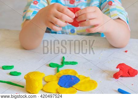 Hands Of Little Girl Making Flower   From Colorful Clay Dough, Plasticine, Home Education Game With