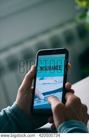 closeup of a young caucasian man, sitting at a table, searching an insurance online with his smartphone, with a simulated search engine