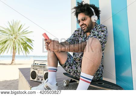 Afro Latin Man Having Fun With Mobile Smartphone And Listening Music With Headphones And Vintage Boo