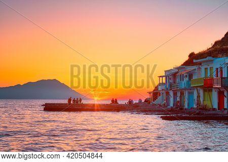 People enjoy scenic sunset in picturesque Klima village above Aegean sea on Milos island in Greece