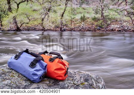 small waterproof duffels on a rocky river shore - Poudre River in a canyon above Fort Collins, Colorado, in springtime scenery