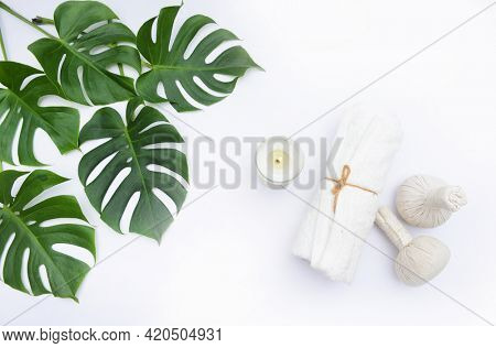 monstera leaves with herbal ball with candle and rolled towel and on white background