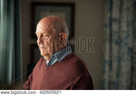 Lonely old man in contemplation near window looking away and thinking. Thoughtful retired man at home looking outside window and contemplating. Pensive senior with sorrow and distressed expression.