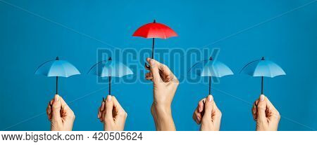 Hand with miniature red umbrella isolated on blue background protect concept. Close up of different women hands holding little tiny blue umbrellas against while a red one differentiate itself.