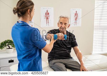 Physiotherapist helping senior man to lift hand weights. Senior man exercising and recovering at nursing home due to epicondylitis. Senior man exercising with professional physiotherapist.