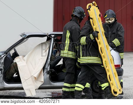 Team Of Firefighters At The Rescue To The Injured With A Yellow Stretcher After The Road Accident