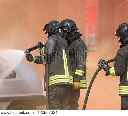 Group Of Firefighters During The Extinguishing Of The Fire Caused After The Road Accident With Prote