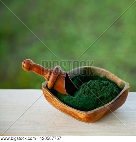 Ground Spirulina in bowl on wood background, top view on dish with superfood