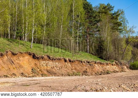 Cutting The Soil Cover With Heavy Machinery. Geological Outcropping In Scenic Area