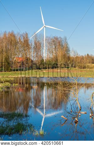 Wind Turbines Near A Forest And Lake With Clear Blue Sky On Background. Renewable Energy Concept, Gr
