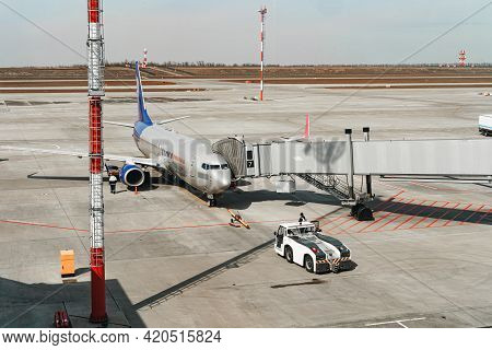 Grey Passenger Aircraft Docked In Airport Getting Ready For Flight