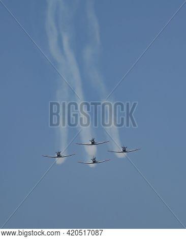 A Four Airplane Aerobatic Team, Performing A Maneuver On An Airshow.