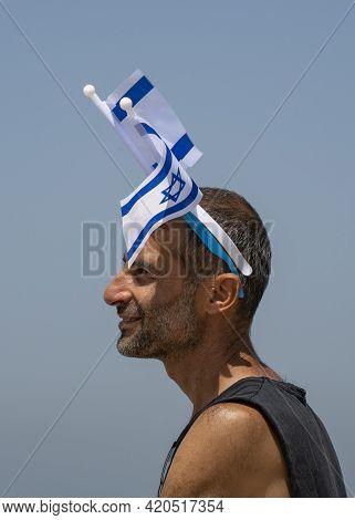 Tel Aviv, Israel - April 15th, 2021: A Man Wearing Israel's National Flags On His Head On Israel's 7