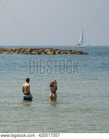 A Young Couple Standing In The Shallow Sea Water, With Sailboats At The Horizon.
