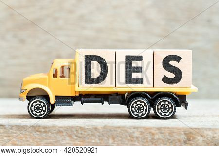 Toy Truck Hold Alphabet Letter Block In Word Des (abbreviation Of Delivered Ex Ship) On Wood Backgro