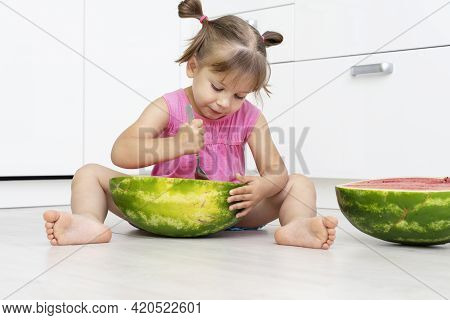 Funny Little Girl Eating Watermelon With Appetite With A Big Spoon Sitting On The Floor In A White K
