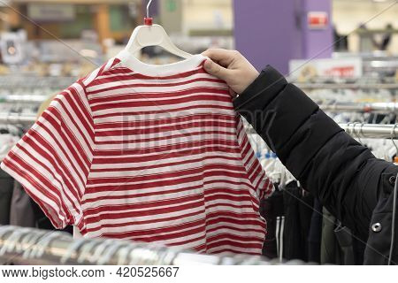 The Girl Chooses Fashionable Bright Clothes. Casual Knitwear For Women.