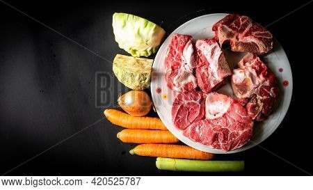Uncooked Food. Raw Beef Bones, And Vegetables On Black Background. Ingredients For Making Beef Broth