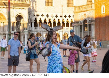 Happy Smiling Girl Feeding Pigeons In Piazza San Marco. Pigeons Sit On The Girl\\\'s Head And Hands.