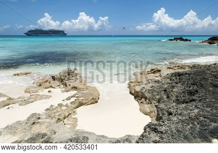 The View Of Rocky Beach On Half Moon Cay Island And A Cruise Ship Drifting In A Background (bahamas)