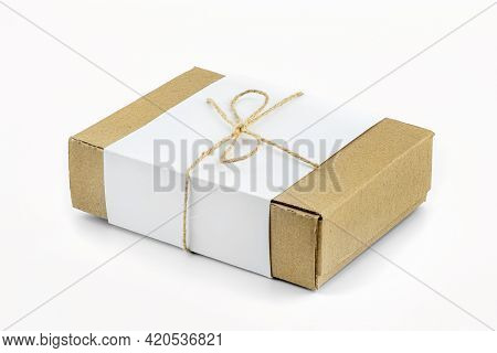 A Small Cardboard Box Made Of Corrugated Cardboard Wrapped With A White Sheet And A Gray String In A